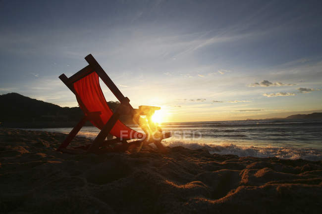 Lounge chair on sand facing sea water at sunset . — Stock Photo