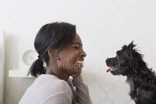 Adolescente jouant avec un petit chien noir, vue de côté . — Photo de stock