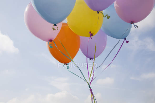 Un mucchio di palloncini colorati che galleggiano in aria contro il cielo blu . — Foto stock