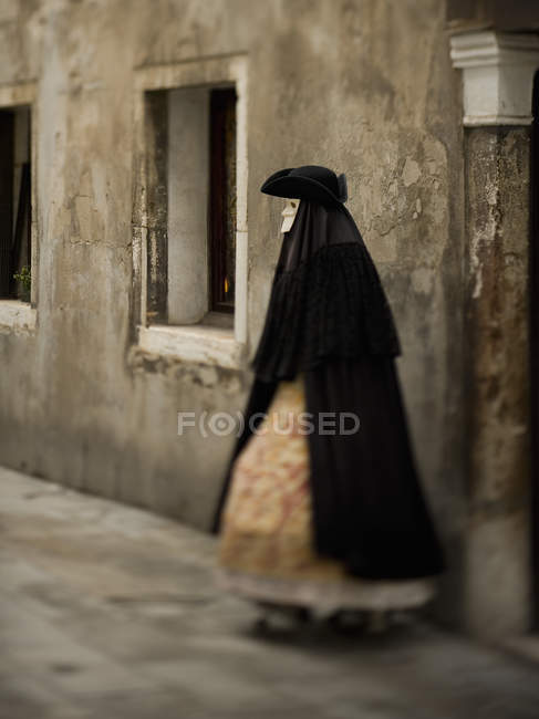 Person in carnival black cloak and dress with petticoats wearing white face mask and tricorn hat. — стокове фото