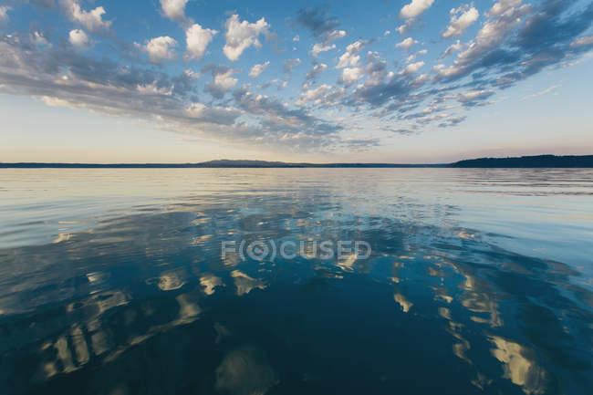 Nuvens dramáticas refletindo no oceano calmo ao anoitecer em Puget Sound, Washington — Fotografia de Stock