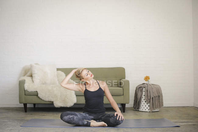 Blonde woman in black leotard and leggings sitting on yoga mat in room — Stock Photo