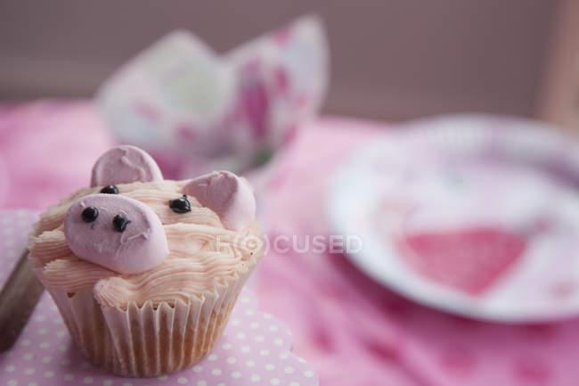 Кекс, прикрашені зображеннями свиней на стіл прикрашена рожевого кольору. — стокове фото