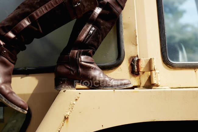 Jovem mulher em botas de couro no capô do trator . — Fotografia de Stock