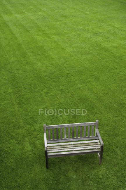 Vue grand angle du banc en bois sur pelouse verte . — Photo de stock