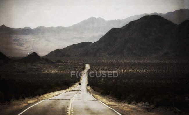 Strada leader gamma di montagne con paesaggi desertici e auto . — Foto stock
