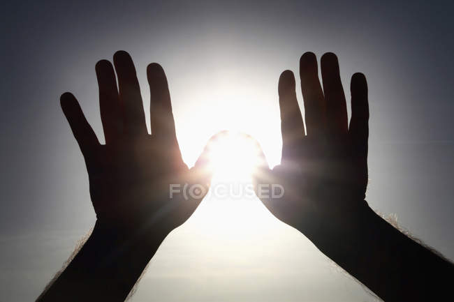 Silhouette of male hands shielding against sun flare. — Stock Photo