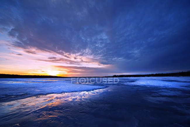 Frozen lake at dusk and view to setting sun on horizon in dramatic sky. — Stock Photo