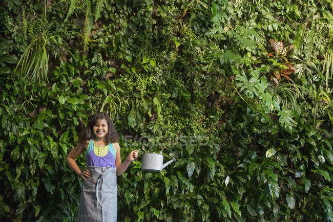 Elementary age girl standing in front of wall covered with ferns and climbing plants with watering can. — Stock Photo