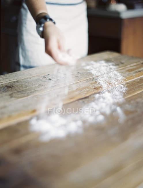 Weibliche Hand verteilt Mehl über hölzerne Tischplatte. — Stockfoto