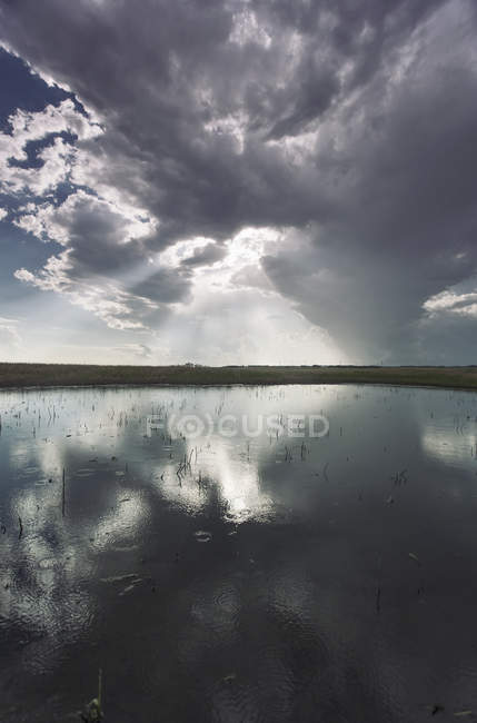 Reflection of dramatic sky in flat surface of lake. — Stock Photo