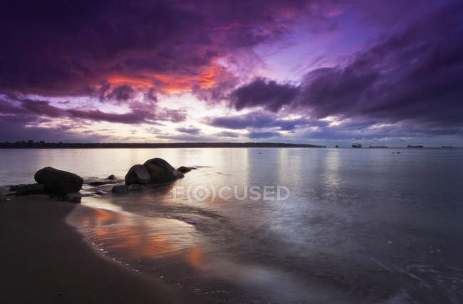 Sunset with orange and purple sky reflecting in calm water. — Stock Photo