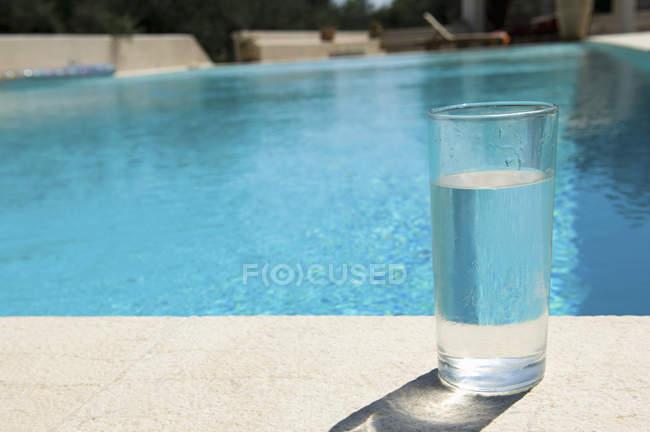 Bicchiere d'acqua sul lato della piscina . — Foto stock