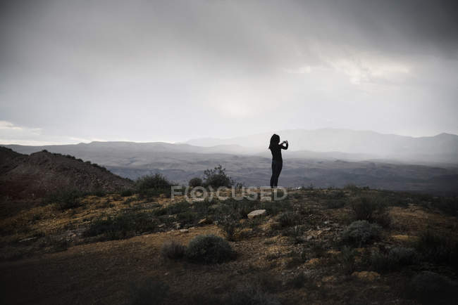 Femme debout dans la prairie sous un ciel nuageux et prenant des photos avec smartphone . — Photo de stock
