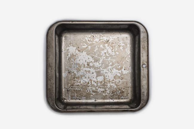 Well used seasoned baking tray on white background — Stock Photo