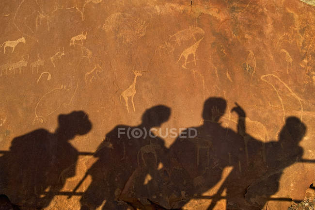 Shadows of people leaning on railing on rock surface of Twyfelfontein in Namibia. — Stock Photo