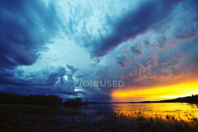 Sunset on horizon over lake with rising storm clouds. — Stock Photo