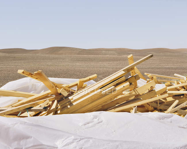 White Tarp Covering Pile Of Wooden Studs Used For Construction.