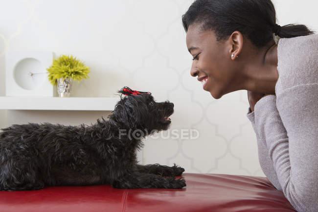 Adolescente che gioca con il piccolo cane nero dell'animale domestico a casa — Foto stock