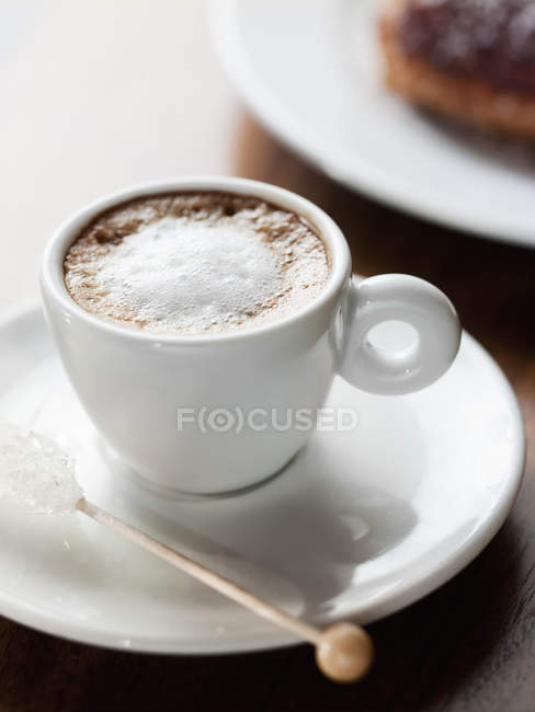 Cup of frothy cappuccino in cup with saucer on wooden table. — Stock Photo