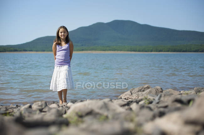 Pre-adolescent girl in white skirt and purple top standing on shore of lake. — Stock Photo