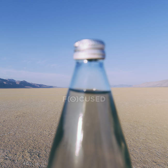 Close-up of bottle of water in landscape of Black Rock Desert in Nevada — Stock Photo