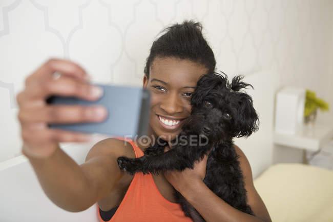 Ragazza adolescente prendendo selfie con piccolo cane nero di smartphone — Foto stock