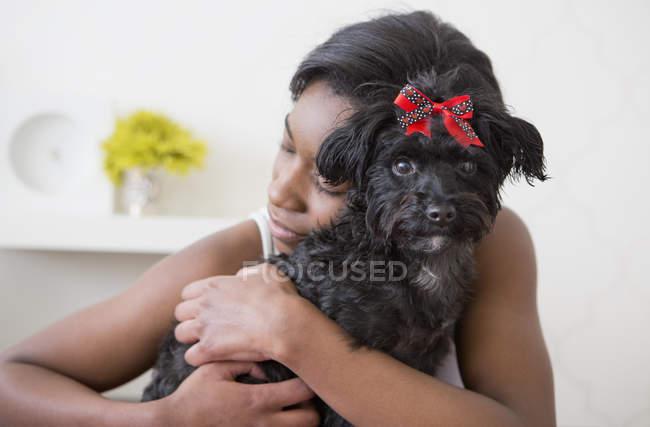 Adolescente che abbraccia piccolo animale domestico cane nero con fiocco rosso — Foto stock