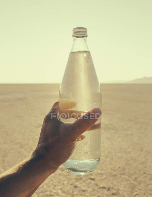Botella de agua de mano masculina en el paisaje del desierto de Black Rock en Nevada - foto de stock