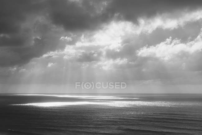 Sunlight through clouds over ocean water — Stock Photo