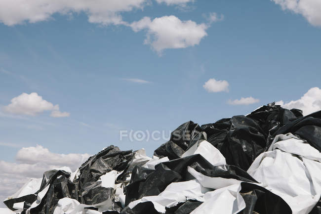 Black and white discarded plastic bags against blue sky. — Stock Photo