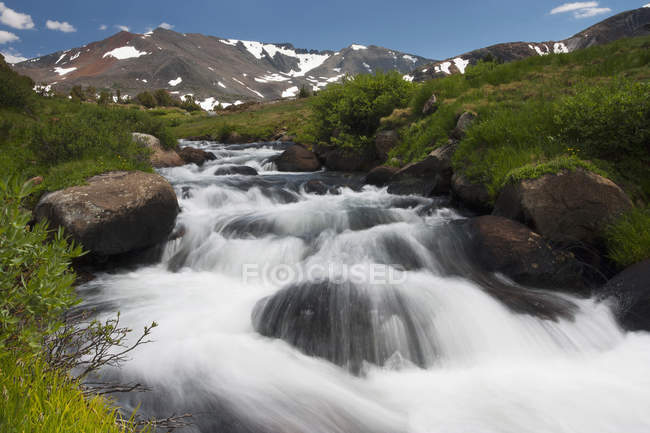 Cascade of fast flowing white water over rocks in valley in mountains. — Stock Photo