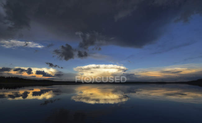 Nubes que reflejan en las aguas tranquilas de Kenosee lake en Canadá. - foto de stock