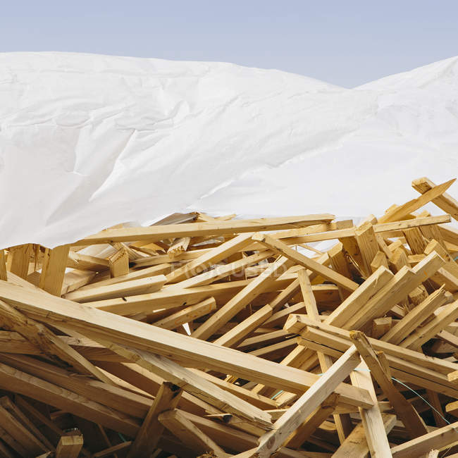 White tarp covering pile of wooden studs used for construction. — Stock Photo