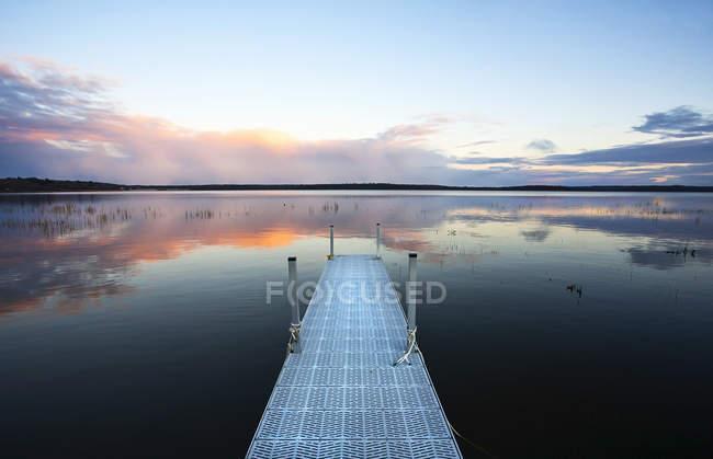 Dock over water of calm lake at sunset in Saskatchewan, Canada. — Stock Photo