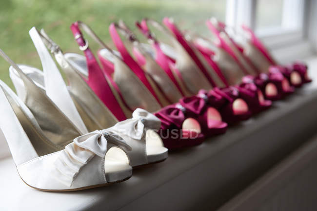 Row of high heeled pink and white shoes. — Stock Photo