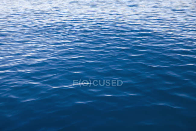 Blue lake water with small ripples, full frame. — Stock Photo