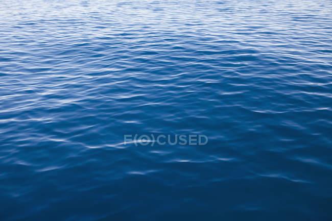 Eau de lac bleue avec de petites ondulations, plein cadre . — Photo de stock