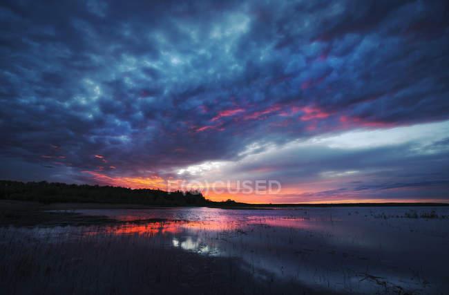 Coucher de soleil sur l'eau calme du lac avec un paysage nuageux crépusculaire au Manitoba, Canada . — Photo de stock