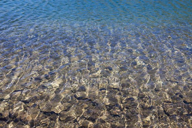 Ondulação na superfície da água com fundo rochoso — Fotografia de Stock