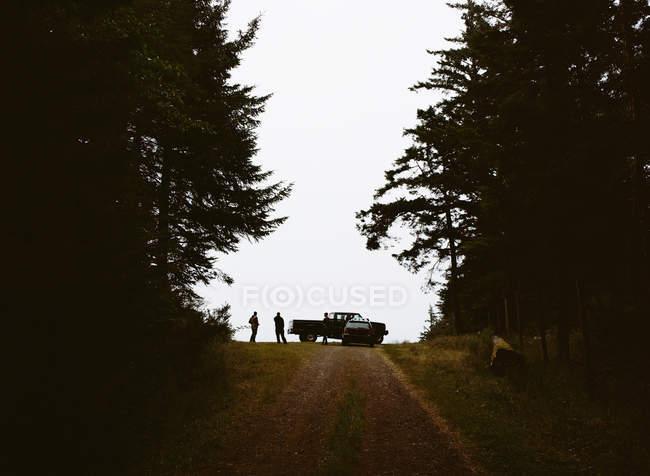 Strada di campagna con veicolo parcheggiato in alto e sagoma di due persone . — Foto stock