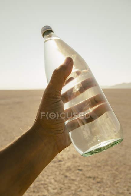 Чоловічої руки, що тримає пляшку води в ландшафті чорний пустелі рок в штаті Невада — стокове фото