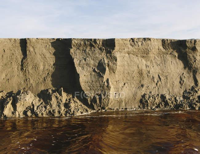 Erodieren Sand Klippe und bewegtem Wasser entlang intertidal Bereich. — Stockfoto