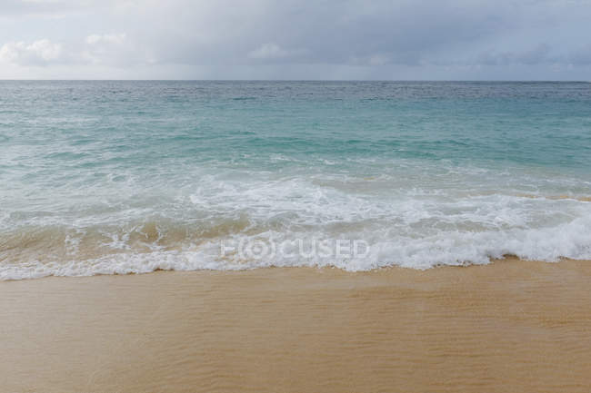 Breaking waves on sand on Pacific Ocean shore. — Stock Photo