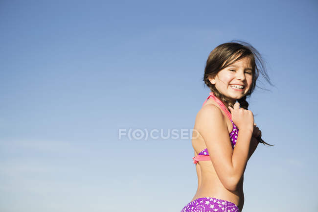 Pre-adolescent girl in pink swimwear with plaited hair against blue sky. — Stock Photo