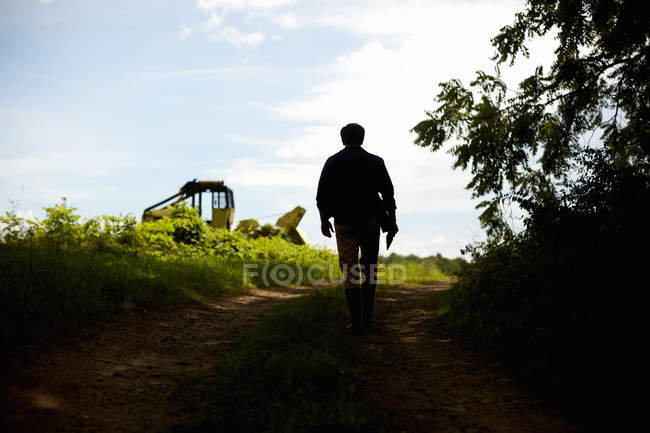 Silhouette of male farmer walking to field with tractor. — Stock Photo