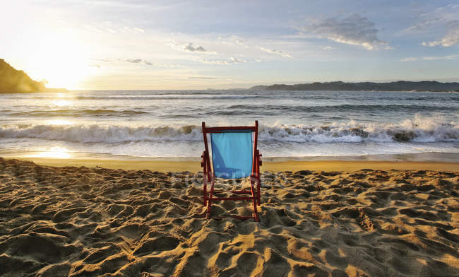 Beach chair on sand and sunset on horizon over seascape. — Stock Photo