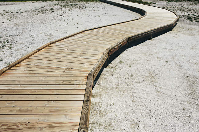 Wooden boardwalk extending across Midway Geyser in Yellowstone National Park. — Stock Photo