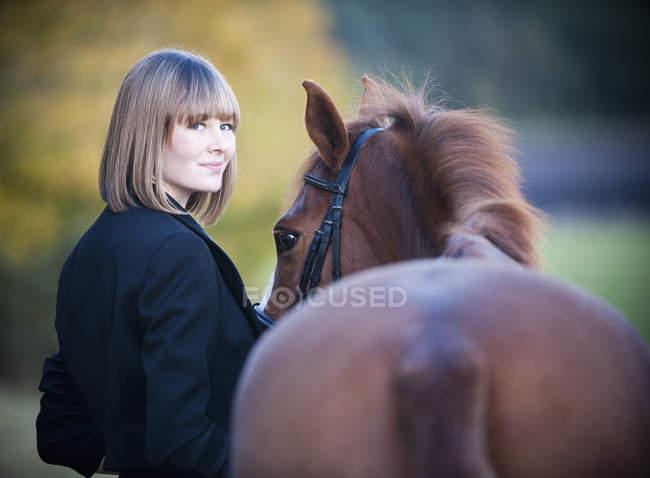 Молодая женщина, ведущая лошадь за уздечкой и смотрящая в камеру . — стоковое фото