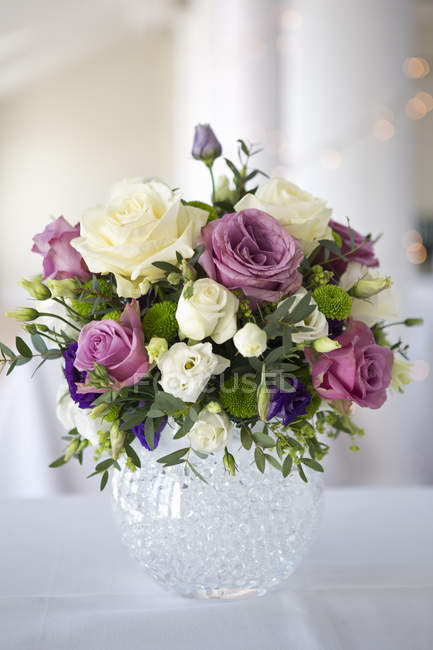 Arrangement of white, pink and purple wedding flowers in glass vase. — Stock Photo